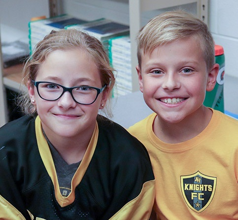 Two students smiling in a classroom