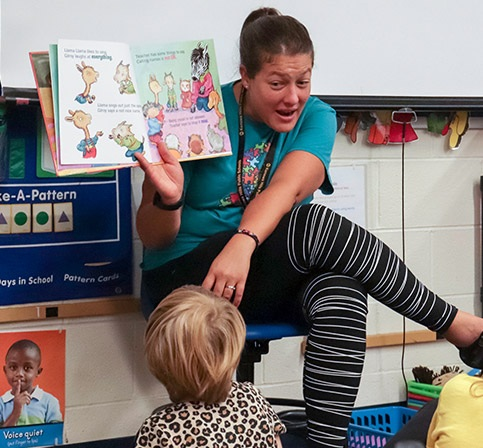 Teacher reading to a group of young students