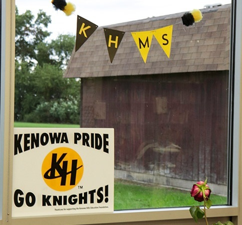Window with Kenowa Hills signs in it. Outside, a barn and green grass
