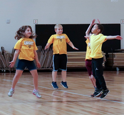 students jumping and playing in the school gym