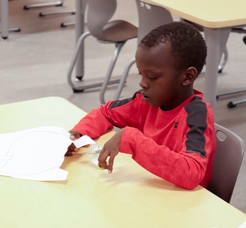 young male student working on an art project cuts out an apple with scissors